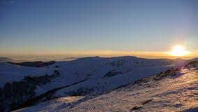 Solnedgång i vinterberglandskapet Arkivfoto