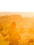 Solnedgång Idrottsman nen med en cykel nära den skogBeautifu frontalen royaltyfri bild