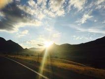 Solnedgång längs vägen Arkivfoton