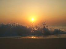 solnedgång med att skumma havsvågor Royaltyfri Fotografi
