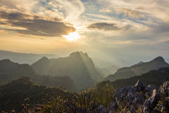 Solnedgång med berglandskap Arkivbild