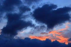 Solnedgång med blåa och karmosinröda moln för mörker - Royaltyfria Bilder