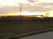 Solnedgång med bron över floden Royaltyfri Bild