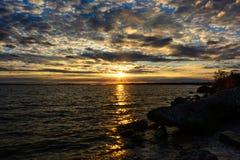 Solnedgång med clounds på Michigan sjön arkivfoto