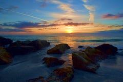 Solnedgång med Contrails över Rocky Seashore royaltyfri fotografi