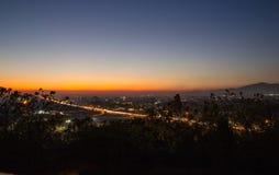 Solnedgång med den upptagna huvudvägen och berg i avståndet royaltyfria bilder