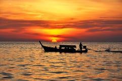 Solnedgång med det Longtail fartyget Arkivbilder