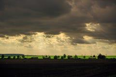 Solnedgång med dramatisk cloudscape över jordbruks- fält och vägen med bilar och lastbilar Royaltyfria Bilder