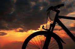 Solnedgång med en cykel Arkivbilder