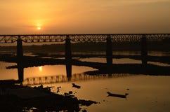 Solnedgång med en drevbro på narmadafloden nära indore, india-2015 Royaltyfri Bild