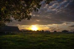 Solnedgång med en ladugård och en äng Fotografering för Bildbyråer