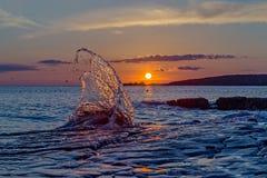 Solnedgång med en stor våg i förgrund Arkivbild