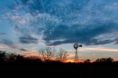 Solnedgång med en väderkvarn i Ingram Texas Royaltyfria Bilder