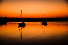 Solnedgång med fiskebåtar på sjön Royaltyfria Bilder
