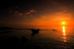 Solnedgång med fiskebåten Arkivbild