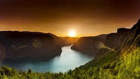 Solnedgång med guld- ljus på en fjord i Norge fotografering för bildbyråer