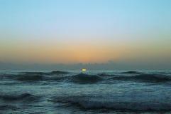 Solnedgång med havvågor arkivfoton
