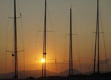 Solnedgång med master av segelbåtar i panelljus arkivfoton