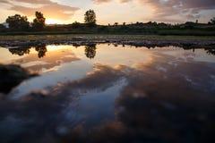 Solnedgång med moln reflekterade på vattnet av en sjö royaltyfria bilder