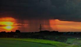 Solnedgång med regn Fotografering för Bildbyråer