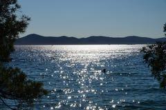 Solnedgång med sikt ut till havet i Kroatien royaltyfria foton