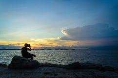 Solnedgång med silhouettestyen Arkivbild