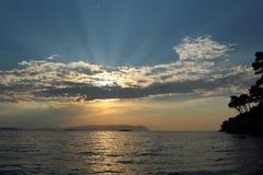 Solnedgång med solsken till och med molnen Arkivbilder