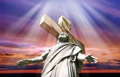 Solnedgång med statyn av korsfäste Jesus Christ Royaltyfria Bilder