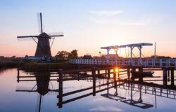 Solnedgång med traditionella holländska väderkvarnar och en träbro i K Arkivbild