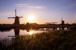 Solnedgång med traditionella holländska väderkvarnar och en träbro i K Royaltyfria Foton