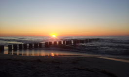 Solnedgång med vågbrytaren vid Östersjön arkivfoto