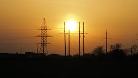 Solnedgång mot bakgrunden av hög-spänning torn elektriska stolpar teknologier arkivfilmer