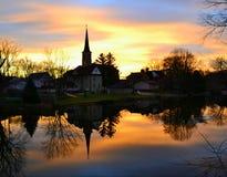 Solnedgång och Chruch reflexioner Arkivbilder