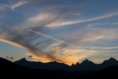 Solnedgång och contrail över berg arkivbild