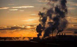 Solnedgång och fabrik Royaltyfri Bild