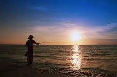 Solnedgång och fiske Arkivfoto