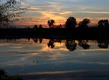 Solnedgång och flod Arkivfoto