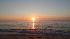 Solnedgång och fotstegen på sanden nära havet Arkivbild