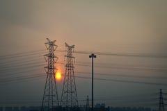 Solnedgång och hög spänningskraftledning Royaltyfri Foto
