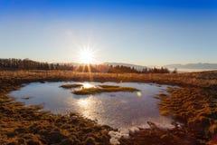 Solnedgång och iskall pöl fotografering för bildbyråer