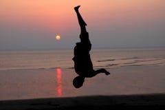 Solnedgång och kontur av en dansare i stranden Arkivfoto