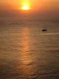 Solnedgång och litet fartyg Royaltyfri Foto