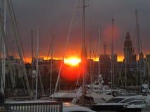 Solnedgång och många fartyg och yachter i en port i Barcelona arkivfoto