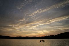 Solnedgång och moln över sjön Arkivbilder