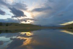 Solnedgång- och molnreflexion på vatten royaltyfria bilder
