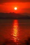 Solnedgång och röd himmel över berget, reflex på floden. Arkivbild