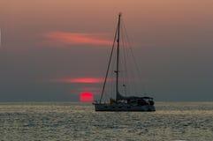 Solnedgång och segelbåt Arkivfoto