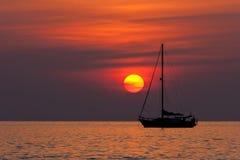 Solnedgång och segelbåt Arkivbilder
