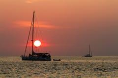 Solnedgång och segelbåtar fotografering för bildbyråer