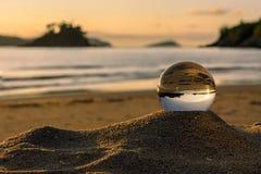Solnedgång och strand i en kristallkula arkivbild